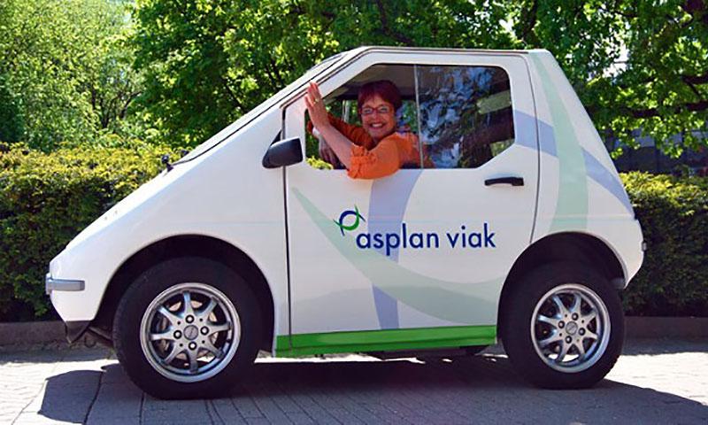 Person som vinker fra en liten elektrisk bil